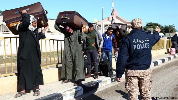 Egyptians walk carrying their belongings towards the Libyan side of the Ras Djir border crossing, on February 23, 2015 as they head to Tunisia for a flight evacuating them back to Cairo. Since the release of a gruesome video showing the beheading of Egyptian Christians by Islamic State group militants on a beach in Libya, Cairo has urged the hundreds of thousands of Egyptians working in Libya to leave, and also chartered planes to fly many of them home from Tunisia, Libya's western neighbor. MAHMUD TURKIA/AFP/Getty Images