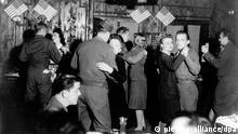 Amerikanische Soldaten beim Tanz mit deutschen Frauen in einer Frankfurter Bar, die mit amerikanischen Fähnchen dekoriert ist. (Aufgenommen zwischen 1945 und 1948).