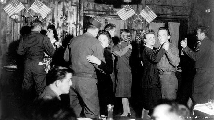 Foto histórica mostra soldados dançando com mulheres em salão decorado com bandeirinhas americanas