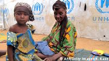 29.03.2014 * Bildunterschrift:TO GO WITH AFP STORY BY REINNIER KAZE A little girl and an elderly woman sit by a UNHCR (United Nation Refugee Agency) tent in the refugee camp of Minawao, on the border of Nigeria at the extreme north of Cameroon, on March 29, 2014. Around 2.500 Nigerian refugees, Christian and Muslims, found shelter in the camp after fleeing the fighting between the Nigerian army and the Islamist rebels of Boko Haram. AFP PHOTO / REINNIER KAZE (Photo credit should read Reinnier KAZE/AFP/Getty Images)