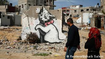 Palestinians walk past a mural of a playful-looking kitten, presumably painted by British street artist Banksy, on the remains of a house that witnesses said was destroyed by Israeli shelling during a 50-day war