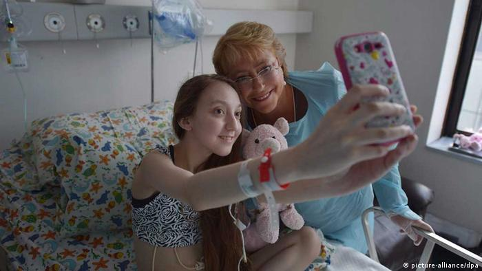 A handout photograph provided by Chilean Presidency on 28 February 2015 shows Chilean president Michelle Bachelet visiting Valentina Maureira, a 14-year girl who suffers cystic fibrosis and asked the Government for permission to die through a YouTube video