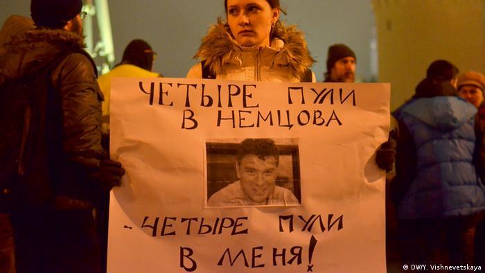 Девушка с плакатом на месте гибели Бориса Немцова