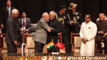 1.3.2015 Indian Prime Minister Narendra Modi, center left, greets Peoples Democratic Party Mufti Mohammed Sayeed after the later was sworn in as the chief minister of Jammu and Kashmir state in Jammu, India, Sunday, March 1, 2015. India's ruling Hindu nationalist party formed a coalition government in Kashmir on Sunday, marking the first time it will hold a leadership position in the disputed Muslim-majority region.(AP Photo/Channi Anand)