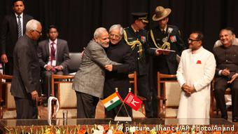 Indian Prime Minister Narendra Modi (center left) greets Mufti Mohammed Sayeed after the latter was sworn in as the chief minister of Jammu and Kashmir state