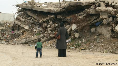 An adult and child stand with their backs towards the camera, facing a pile of rubble in Gaza (Photo: Tania Krämer, DW)