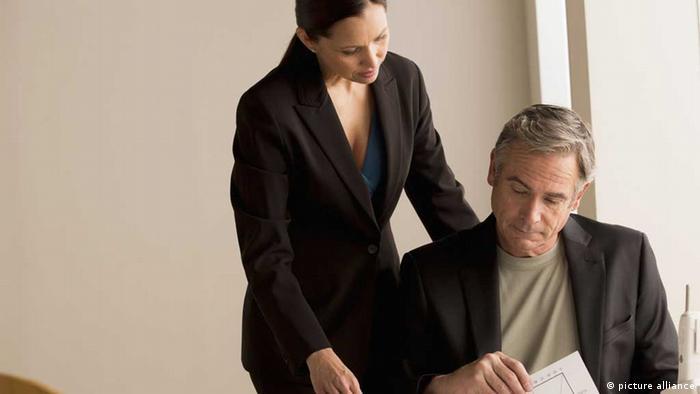 Eine Frau beugt sich über einen Mann, der an einem Schreibtisch arbeitet