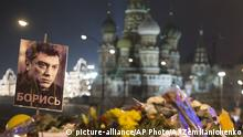 02.03.2015 * People walk to pay their respects at the place where Boris Nemtsov, a charismatic Russian opposition leader and sharp critic of President Vladimir Putin, was gunned down on Friday, Feb. 27, 2015 near the Kremlin, with St. Basils Cathedral is in the background in Moscow, Russia, Monday, March 2, 2015. The investigation into the killing of Boris Nemtsov, a fierce critic of Russian President Vladimir Putin who was gunned down not far from the Kremlin, faced conflicting reports Monday about possible surveillance footage of his slaying. Words on a portrait and a poster reading 'Fight!' (AP Photo/Alexander Zemlianichenko)