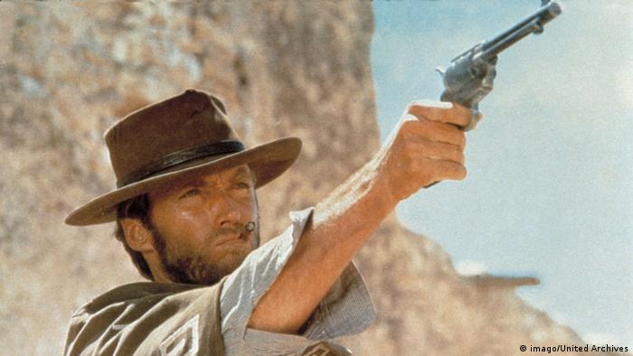 Clint Eastwood firing a gun in the desert