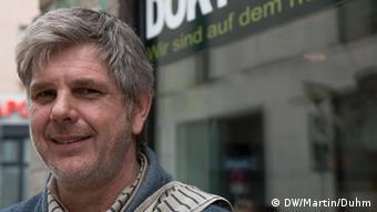 Ο Λαρς Σάινμαν έχει κατάστημα με προϊόντα κάνναβης και είναι ο πρώτος Γερμανός που πήρε φαρμακευτική κάνναβη από το φαρμακείο επειδή πάσχει από το σύνδρομο Τουρέτ
