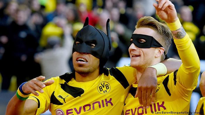 Aubameyang und Reus celebrate scoring a goal in Batman and Robin masks