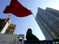 A security guard stands on a construction site in Beijing Tuesday, Dec. 20, 2005. China sharply raised the official size of its economy Tuesday after taking into account emerging service industries, saying its output last year was 16.8 percent higher than previously reported. (AP Photo/Greg Baker)