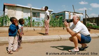 A white man takes a photo of two black children in the Soweto township