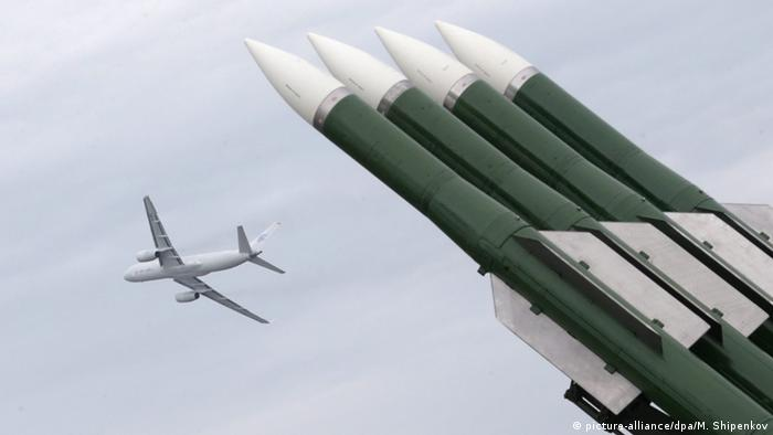 A plane flies in the sky above a Buk missile system