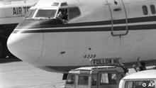 A Shiite Moslem hijacker points his pistol toward an ABC news media crew from the window of the cockpit of the Trans World Airlines jet as the American television crew approaches the jet for an interview at Beirut International Airport, Lebanon, Wednesday, June 19, 1985. Gunmen hijacked TWA flight 847 carrying 153 people on June 14. The ordeal lasted 17 days, with one passenger killed. (AP Photo/Herve Merliac)