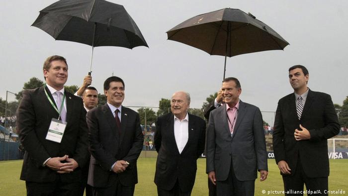 Alejandro Dominguez, Horacio Cartes & Joseph Blatter stand under umbrellas while inspecting a football pitch