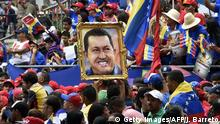 March 5, 2015 Bildunterschrift:People hold a portrait of former Venezuelan president Hugo Chavez during a ceremony commemorating the second anniversary of his death in Caracas on March 5, 2015. AFP PHOTO/JUAN BARRETO (Photo credit should read JUAN BARRETO/AFP/Getty Images)