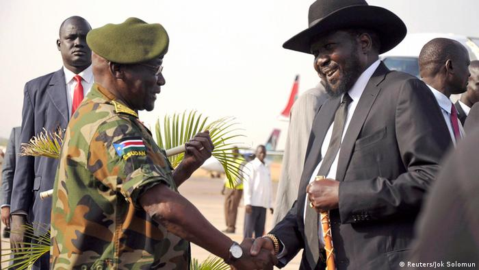 Former South Sudan military chief, Paul Malong, shakes hands with President Salva Kiir