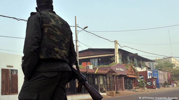 A member of the security forces stands near the La Terrasse restaurant, as seen with the blue curtains, in Bamako on March 7, 2015.