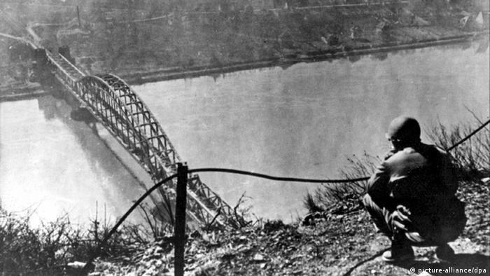 Март 1945: американски войник наблюдава от височината моста над Рейн край град Ремаген