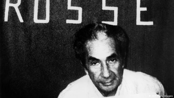 Brigadas Vermelhas sequestraram e mataram o ex-primeiro-ministro italiano Aldo Moro. Imagem em preto e branco mostra Moro em frente a uma bandeira das Brigadas Vermelhas, após ser raptado