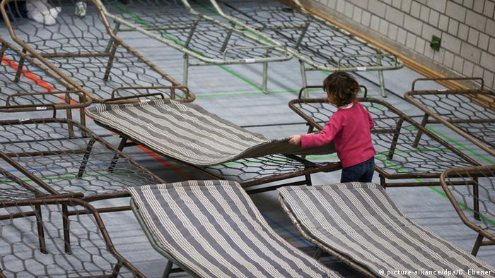 A small child lays a mattress on a camp bed in a refugee shelter.(Photo: dpa)