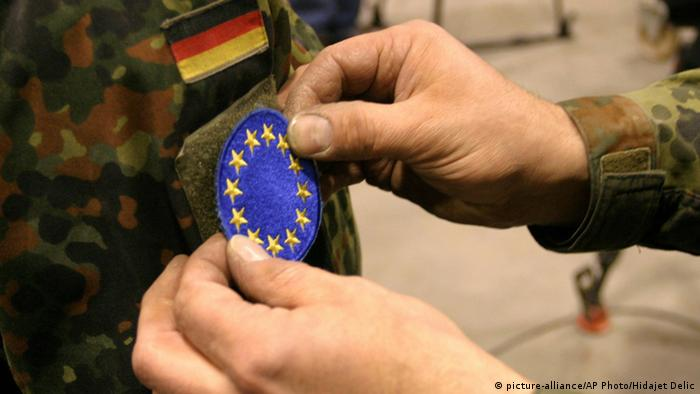 A German Army officer, member of peacekeeping forces in Bosnia, places a new EUFOR signet on the uniform sleeve of a fellow soldier
