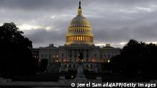 A man walks near the US Capitol building before sunrise on the morning after a bipartisan bill was passed by the House and the Senate to reopen the government and raise the debt limit, on October 17, 2013 in Washington, DC. US President Obama signed the bill into law, that will fund the government until January 15, 2014 and allow the government to pay bills until February 7, 2014. AFP Photo/Jewel Samad (Photo credit should read JEWEL SAMAD/AFP/Getty Images)