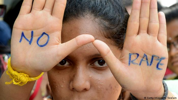 woman holding up hands showing words no and rape (Getty Images/N. Seelam)