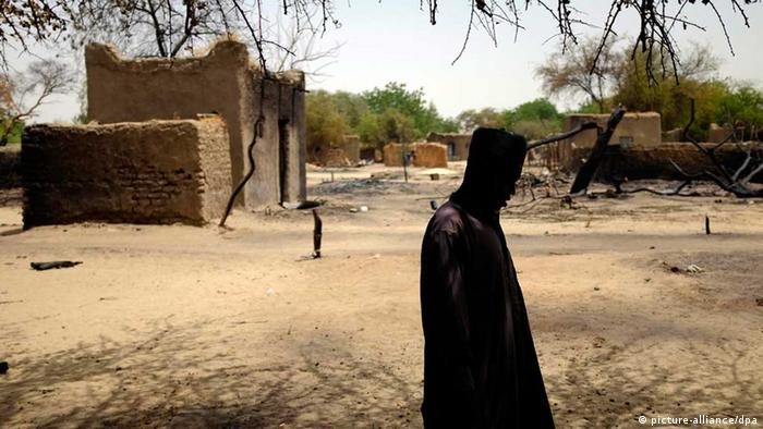 A man walks past a burnt house in Chad