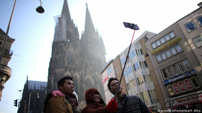 Tourists with a selfie-stick in front of the Cologne Cathedral (Copyright: Oliver Berg/dpa)