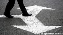 A person taking a step on arrows painted forward and backward on a street (imago/Action Pictures)