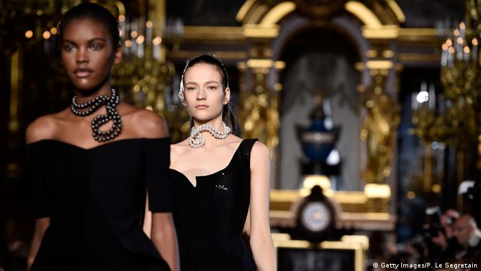 Models wearing black dresses and twisted pearl necklaces walk the runway during the Stella McCartney show at Paris Fashion Week, 2015