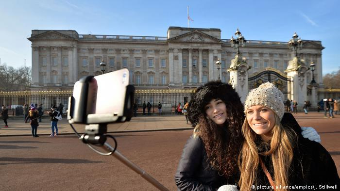 Two women outside Buckingham Palace in London, UK, taking a selfie on a smartphone, or calling home (picture alliance/empics/J. Stillwell)