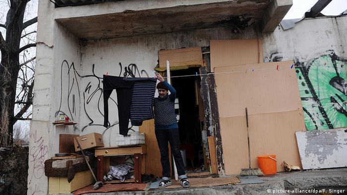 A Roma man hangs washing on a line outside a rundown house