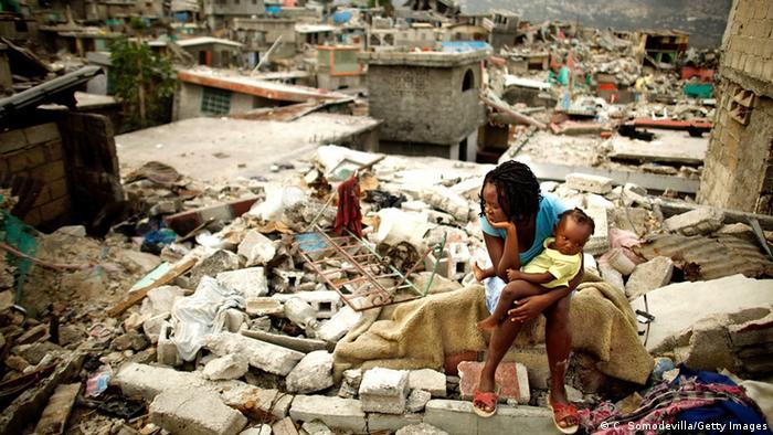 Mulher com criança no colo está sentada em cima de destroços de uma casa. Ao fundo, destroços de outras várias casas destruídas.