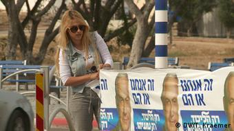 Woman putting up Likud campaign posters