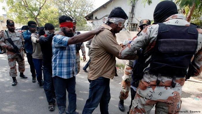 Paramilitary soldiers escort blindfolded men, who were detained during Wednesday's raid on the Muttahida Qaumi Movement (MQM) political party headquarters, after presenting them before an anti-terrorism court in Karachi March 12, 2015 (Photo: REUTERS/Akhtar Soomro)