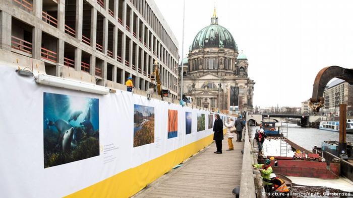 Berlin's cathedral in the distance as people walk along the river looking at the images on show