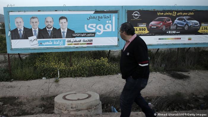 Wahlkampf in Israel: Ein arabischer Israeli vor einem Wahlplakat der Vereinigten Arabischen Liste - Foto: Ahmad Gharibaldi (AFP)