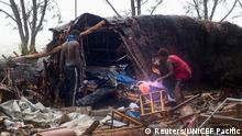 Local residents look through the remains of a small shelter in Port Vila, the capital city of the Pacific island nation of Vanuatu March 14, 2015. Winds of up to 250 kilometers an hour (155 mph) ripped metal roofs off houses and downed trees in Vanuatu on Saturday, as relief agencies braced for a major rescue operation and unconfirmed reports said dozens had already died. Witnesses described sea surges of up to eight meters (yards) and flooding throughout the capital Port Vila after the category 5 cyclone named Pam hit the country late on Friday. REUTERS/UNICEF Pacific/Handout via Reuters (VANUATU - Tags: DISASTER ENVIRONMENT) ATTENTION EDITORS - THIS PICTURE WAS PROVIDED BY A THIRD PARTY. REUTERS IS UNABLE TO INDEPENDENTLY VERIFY THE AUTHENTICITY, CONTENT, LOCATION OR DATE OF THIS IMAGE. FOR EDITORIAL USE ONLY. NOT FOR SALE FOR MARKETING OR ADVERTISING CAMPAIGNS. NO SALES. NO ARCHIVES. THIS IMAGE WAS PROCESSED BY REUTERS TO ENHANCE QUALITY, AN UNPROCESSED VERSION WILL BE PROVIDED SEPARATELY