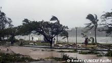 Debris is strewn across a road as local residents walk nearby in Port Vila, the capital city of the Pacific island nation of Vanuatu March 14, 2015. Winds of up to 250 kilometers an hour (155 mph) ripped metal roofs off houses and downed trees in Vanuatu on Saturday, as relief agencies braced for a major rescue operation and unconfirmed reports said dozens had already died. Witnesses described sea surges of up to eight meters (yards) and flooding throughout the capital Port Vila after the category 5 cyclone named Pam hit the country late on Friday. REUTERS/UNICEF Pacific/Handout via Reuters (VANUATU - Tags: DISASTER ENVIRONMENT) ATTENTION EDITORS - THIS PICTURE WAS PROVIDED BY A THIRD PARTY. REUTERS IS UNABLE TO INDEPENDENTLY VERIFY THE AUTHENTICITY, CONTENT, LOCATION OR DATE OF THIS IMAGE. FOR EDITORIAL USE ONLY. NOT FOR SALE FOR MARKETING OR ADVERTISING CAMPAIGNS. THIS PICTURE IS DISTRIBUTED EXACTLY AS RECEIVED BY REUTERS, AS A SERVICE TO CLIENTS. NO SALES. NO ARCHIVES