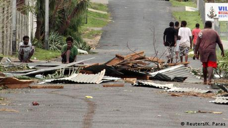 Local residents sit near debris on a road outside a hospital after Cyclone Pam hit Port Vila (photo: REUTERS/Kris Paras)