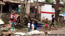A woman carrying a baby stands with children outside homes damaged by Cyclone Pam, on a street surrounded by debris in Port Vila, the capital city of the Pacific island nation of Vanuatu March 15, 2015. The first aid teams to reach Vanuatu on Sunday encountered widespread devastation and authorities declared a state of emergency after the monster cyclone tore through the vulnerable Pacific island nation. With winds of more than 300 kph (185 mph), Cyclone Pam razed homes, smashed boats and washed away roads and bridges as it struck late on Friday and into Saturday. Aid workers described the situation as catastrophic. The count of confirmed deaths was at 10 with 20 people injured. But those numbers were almost certain to rise as rescuers reached the low-lying archipelago's outlying islands. REUTERS/Kris Paras (VANUATU - Tags: DISASTER ENVIRONMENT TPX IMAGES OF THE DAY)