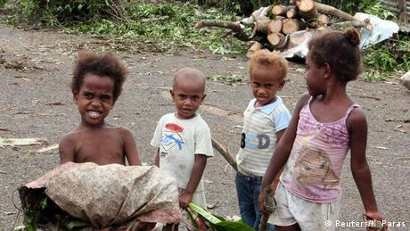 Children stand in front of debris on a street near their homes after Cyclone Pam hit Port Vila (photo:. REUTERS/Kris Paras)