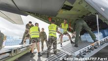 Privates load water bottles into a French Army logistical transport plane bound for Vanuatu, transporting food, water and relief, at the Aerial Military Base Lieutenant Paul Klein (formerly known as La Tontouta), north of Noumea, New Caledonia, on March 15, 2015. Cyclone-devastated Vanuatu declared a state of emergency on March 15 as relief agencies scrambled to get help to the Pacific nation amid reports entire villages were blown away after being hammered by Super Cyclone Pam. AFP PHOTO / FRED PAYET (Photo credit should read FRED PAYET/AFP/Getty Images)