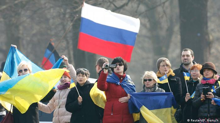 A Russian flag is waved behind Ukrainian supporters during a visit by Ukrainian President Petro Poroshenko in Berlin