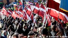 People hold flags as they participate in the annual procession commemorating the Latvian Waffen-SS (Schutzstaffel) unit, also known as the Legionnaires, in Riga March 16, 2015. The Legionnaires are commemorated annually for fighting against the Soviet occupation of Latvia, but the Nazi connection has caused great controversy abroad, particularly in Russia. REUTERS/Ints Kalnins (LATVIA - Tags: ANNIVERSARY MILITARY)