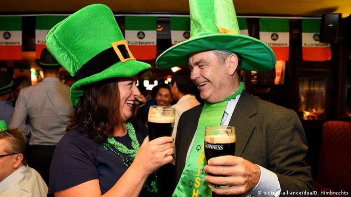 Two people holding pints of Guinness and wearing leprechaun hats