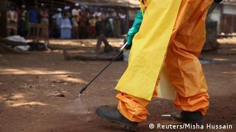 Un agent de santé en train de désinfecter contre Ebola en Guinée